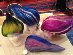 Finished wigs; most were dried upside down or with supports holding the hair up until dry.