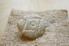 Handcrafted in an elegant shimmery ivory pearl, this brooch / pin is antiqued with rose gold/copper antiquing with an embossed floral carving