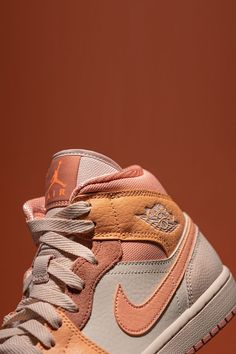 """Complementing shades of pink, rust, and orange across the Women's Air Jordan 1 Mid """"Apricot's"""" leather, suede, and mesh panels give a decidedly premium look—one that's not uncommon to one of Jordan's more exploratory sneakers. Jordan 1 Mid, Air Max, Air Jordans, Street Wear, Nike, Sneakers, Rust, Leather, Shades"""