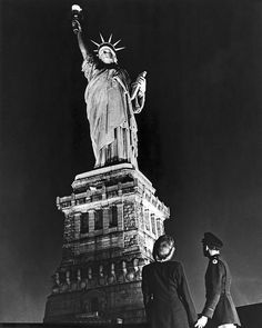 New York, New York: May 8, 1945. A soldier and his companion gaze up on V-E Day at the Statue of Liberty after it was illuminated, except for a brief period on D-Day, for the first time since the Pearl Harbor attack.