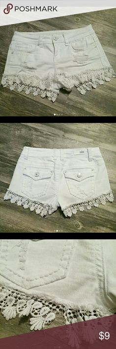 """White Denim Destructed Shorts Size 3 Junior white denim shorts with crocheted lace trim    2"""" - 2.5"""" Inseam with crocheted lace.  Back leg of crochet trim does have a tear, as pictured in 3rd pic, but not very noticeable when worn. Could easily be sewn. Super cute! Almost Famous Shorts Jean Shorts"""