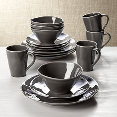 Our most coveted casual dinnerware collection recalls the warm hospitality of Portugal's quaint seaside cafes. Glazed dark grey, each free-form stoneware item in the four place settings is hand-antiqued at the rim by Portuguese artisans.