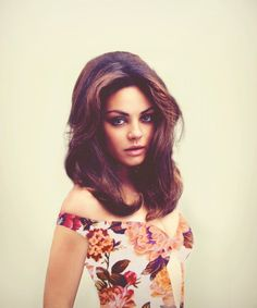 Mila Kunis looks like a bombshell in this photo. The print on her with the hair and eyes is awesome!