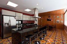 Decoração de casa com materiais nobres e acabamentos sofisticados na cozinha banqueta preta, armário cinza, revestimento vermelho.