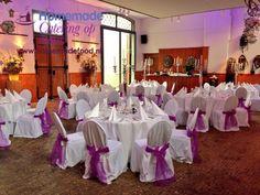 Huwelijksdiner opstelling in het Grote Salon van het Koetshuis te Kasteel Keukenhof. Ronde tafels gedekt met fris wit linnen en zilveren kandelaren. Wit afgerokte stoelen met paarse strikken. Een feestelijke setting voor het bruidspaar. Homemade Catering op Maat denkt graag mee.