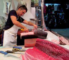 Es un vendedor que cortó el pescado. Estos vendedores son carniceros muy cuidadosos ¡pero son muy rápidamente! También en el imagen hay el pescado mas grande del mercado--el atún.