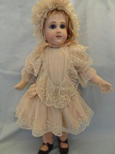 Rare and seldom seen is this enchanting French doll made by the firm of Schmidt & Fils circa 1880.  She stands 18 inches tall and has the Schmidt