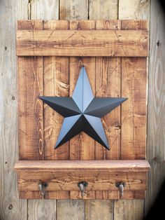 This is a solid wood piece that has been painted or stained and distressed for the farmhouse look. It measures approximately 17 x 23 and it has a metal barn star in the center (Black, Blue, Red, or Rusty). Below the 3.5 wide shelf are three rustic cast iron wall hooks. There are