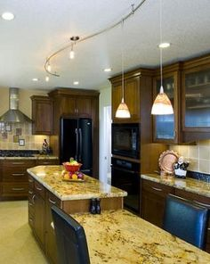 combination of can lights and track. http://www.interiorlightingoptions.com/wp-content/uploads/2012/04/track-lighting-kitchen.jpg