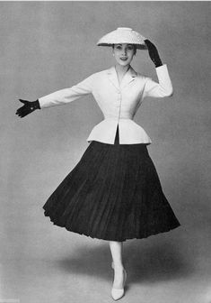 This is an image of the 'New Look' in the 50s that was popularized by designer Christian Dior. The look consisted of soft shoulders, an emphasized tiny waist and accentuated hips. This 'New Look' was essential just and 'old look' revived and updated for this time. It represented a new outlook after WW2.
