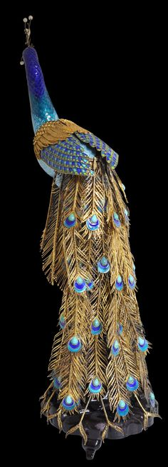 View 1: This rather extraordinary and well-observed model of a peacock is made from enamelled and gilded (gold-plated) silver and silver filigree. The tail feathers are also inset with large pear-shaped turquoise cabochons and the crest on the head is of pearls beaded onto fine silver wire springs.