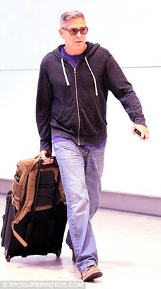 Happy days : The 53-year-old actor looked fresh-faced and relaxed as he wandered through the arrivals terminal, in spite of his long transatlantic flight