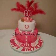 Two tiered pink and white cowgirl themed sponge cake with fondant decorations and feather spray.
