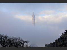 la tour Eiffel émerge des nuages au matin du 27 novembre, jour d'hommage national aux victimes des attentats de Paris.