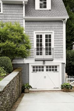 Add Iron Detailing - Pour On the Cottage Charm - Southernliving. A Juliet balcony embellishes the exterior and allows for French doors off the new home office. Iron pulls and strap hinges finish the carriage-style garage door. Balcon Juliette, Juliette Balcony, Interior Exterior, Exterior Doors, Rustic Exterior, Cape Cod Exterior, Craftsman Exterior, Craftsman Style, Exterior Paint
