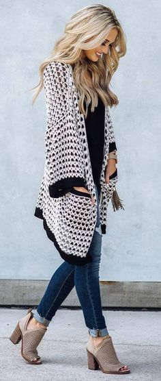 Chic black and white cardigan over black top and blue jeans.