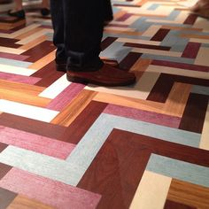 A contemporary take on traditional parquet flooring as seen at the Mannington showroom at NeoCon 2012. The wow factor is provided by the unusually fashion-forward mix of color and wood tones - the modern rose and blue with the trad wood textures.