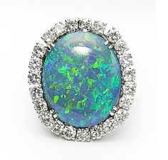 An opal and diamond ring centering an oval-shaped black opal, weighing 11.53 carats, within a round brilliant-cut diamond surround; estimated total diamond weight: 1.90 carats; mounted in eighteen karat white gold.