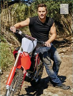 Posing on a dirt bike, Chris Pratt sports a Calvin Klein t-shirt, PRPS Goods & co jeans, Red Wing Heritage boots, and a TAG Heuer watch.