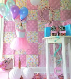 Quilt background, some balloons, a dance costume and a side table with some items displayed (maybe dance shoes)