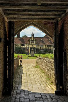 Leaving the Ightham Mote Courtyard over the West Bridge toward the 15th century Cottages in the distance. Kent, England, UK