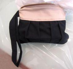 Kleine Pochette aus feiner Baumwolle mit Handgelenkband und Reißverschluss.