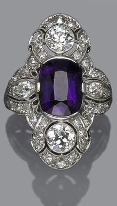 An art deco amethyst and diamond ring, circa 1925 centering an oval-shaped amethyst; signed D. Co.; estimated total diamond weight: 2.50 carats; mounted in platinum. by Bella Donna