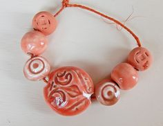 The set consists of =1 bead-lentil porcelain , handcarved ,this bead are hollow and weigh very little , have red glaze , measures 27 x 27 mm. -4 beads hand-carved and 2 round beads,have red glaze . By Mª Carmen Rodriguez Martinez ( Majoyoal ) https://www.facebook.com/groups/CeramicArtBeadMarket/