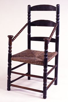 "1700-1725 American Armchair in Historic Deerfield, Deerfield - From the curators' comments: ""Slat-back or ladder-back armchair in maple, repainted green-black in the 19th century, with a rush seat and old blue material cushion. The chair, which would have had finials originally on top of the turned back posts, has double ball turnings between the upper two arched slats."""
