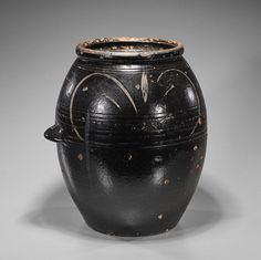 "Large, possibly antique, Korean glazed pottery jar; of ovoid form with a loop handle low on body, with several concentric bands and incised characters to top (h: 15"")."