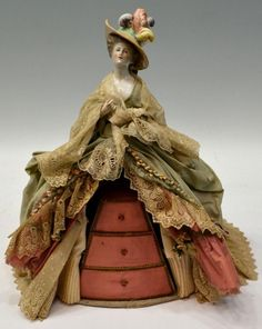 "Unusual vintage figural jewelry box, china head top of a beauty wearing feathered hat, her lace and gown trimmed with flowers, concealing a jewel box of three graduated drawers, loss of thumb on one hand, 18.5""h, 3lbs Start Price: $50.00"