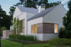 Linear garapa wood window accents coordinate with the custom metal shutters beyond, standing seam metal roof above, and the horsetail reed landscaping across the front of the house.