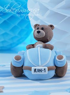 Nalle ajaa synttärijuhliin. Kakun koriste sokerimassasta. / Teddy bear is driving to a party. Cake decoration made from sugar paste.