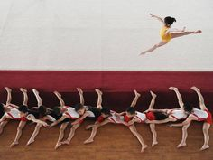 July 10, 2012: Young male gymnasts (bottom) stretch their legs as a female - The Independent
