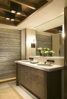 Dark wood vanity with a light colored concrete countertop.  Clean lines juxoposed with the roughness of the stone wall.