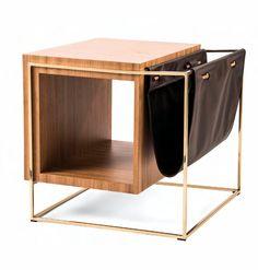 MESA CUBO Lattogg Dueño de una estética sencilla pero contundente, este mueble combina las funciones de mesa auxiliar y revistero. La estructura rectangular, desarrollada en metal cromado de color dorado –que nos remite a su uso en los muebles auxiliares de los años 50 y 60– sostiene tanto al sólido cubo de madera como al sencillo corte de cuero que da forma al revistero. Madera, metal y cuero entablan un diálogo material que resulta en un armonioso juego de..