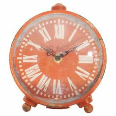 "Antiqued iron table clock with a Roman numeral dial.  Product: Table clockConstruction Material: Iron and glassColor: OrangeFeatures:  Roman numeral dialAntiqued finish Accommodates: Batteries - not includedDimensions: 6.75"" H x 6"" W x 2"" D"