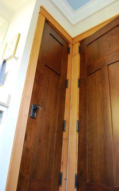 Custom walnut bathroom doors showcase glass knobs and are surrounded by Douglas fir molding.