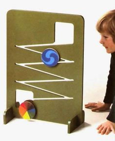 """Rollbahn (""""roller-run"""") color and movement toy, designed by Mike Ayres and Roger Limbrick, Switzerland, 1984, by Naef Spiele. The colored discs, with various designs and patterns, take almost a minute and a half to completely descend the zig-zag pattern of the frame, slowly mesmerizing with alternating shapes and visual trickery. #toy"""