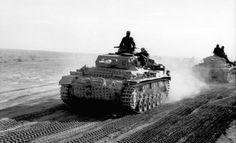 Panzerkampfwagen III (5 cm Kw.K. 38 L/42) Ausf. H (Sd.Kfz. 141) Un Panzer III Ausf. H sur une piste d'Afrique du Nord, probablement en Cyrénaïque. Le mode de fixation des patins de chenilles de rechange est encore effectué via les crochets avant de remorquage. Il disparaîtra ensuite par l'adjonction d'une barre métallique horizontale sur le glacis avant. Les roues de routes supplémentaires, déposées sur les maillons de chenilles, seront alors placés sur le côté ou à l'arrière du blindé (on…