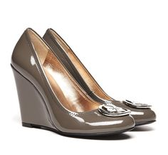 Close toe wedge, patent finish and metal medallion.