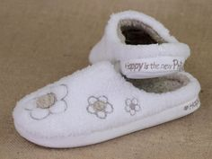 """They say that beauty comes from within and we'd like to second that emotion with the introduction of our new """"Happy is the New Pretty"""" fluffy slippers.  Adorable flowers adorn the toe and drape along the side for added joy in these cozy, cozy slippers.  With a deep 'soul' of memory foam, our new """"Happy is the New Pretty"""" slippers are the perfect gift for anyone who enjoys walking on clouds."""