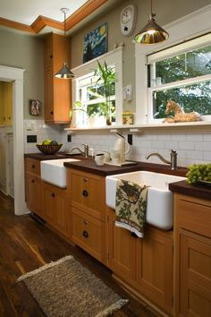 Wood cabinets and countertops have a white subway tile backsplash for counterpoint, and two farmhouse sinks. Bungalow Kitchen, Bungalow Homes, Craftsman Kitchen, Craftsman Homes, Craftsman Style, Cabinets And Countertops, Built In Cabinets, White Kitchen Cabinets, Wood Cabinets