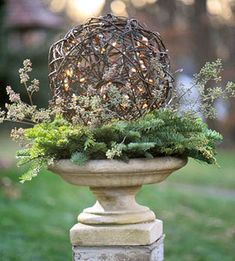 Garden urn with lighted vine ball and greens.