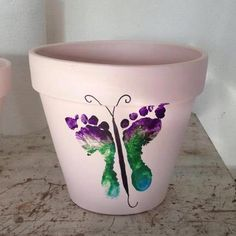 Butterfly footprints on a flower pot. Could make one each year, using bigger pots as needed as your child grows