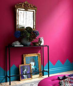 Décoration petit salon. Peinture murale rose fushia, plinthes peintes avec motif sur mur en bleu vif. Console fer noir