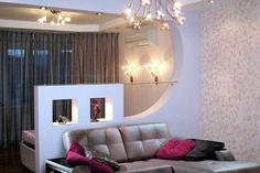 ТОП-10 идей зонирования гостиной. Ниши. Это оптимальный вариант для зонирования гостиной и спальни или кабинет. Вполне гармонично смотрится ниша возле изголовья кровати: чтобы визуально разнообразить пространство можно сделать акцент на элементах декора. Поставьте в нишу длинные вазы с цветами, красивую лампу, повесьте картины, тогда и внимание будет привлечено к той части комнаты, которую вы хотите подчеркнуть.