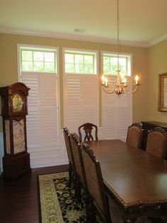 Plantation shutters with open transom in a dining room.  Beautiful!
