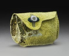 Untitled, C83 2008 4.5″ x 6.5″ x 3.5″ merino and finn/rambouillet wool fiber, cotton and waxed linen thread, repurposed plastic button; wet felting techniques, naturally dyed with weld and indigo, free-motion machine embroidered, hand stitched construction photo credit: Tom Mills collection of Zita Simutis Drillings