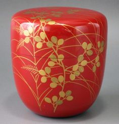 Rlacquered wood tea caddy (natsume) with gold maki-e floral design; chū-natsume (medium size jujube fruit) shape, modern